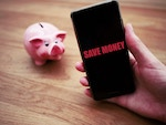 "Piggybank and a mobile with ""Save Money"" text on the screen"