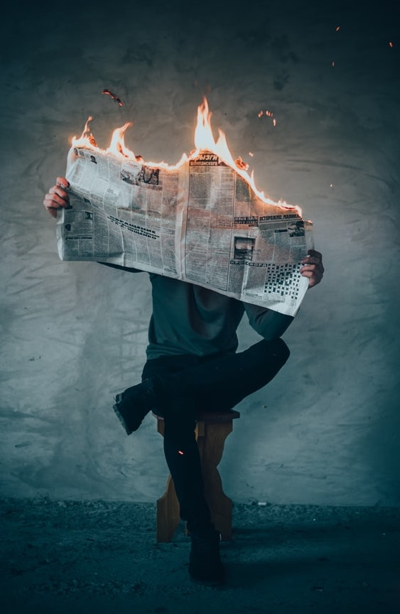 Man sitting and reading newspaper, that are on fire.