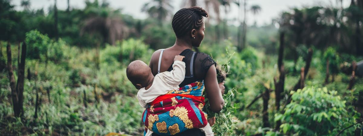Black woman carrying a baby on her back