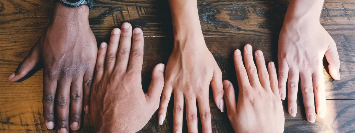 Hands with different skin tones lying next to each other