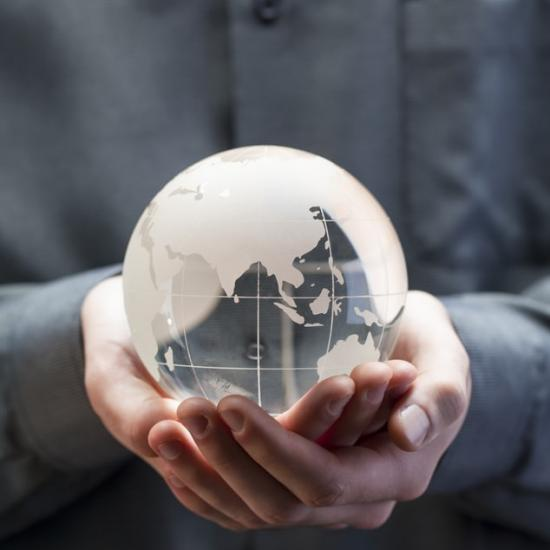 Person holding a glass earth globe