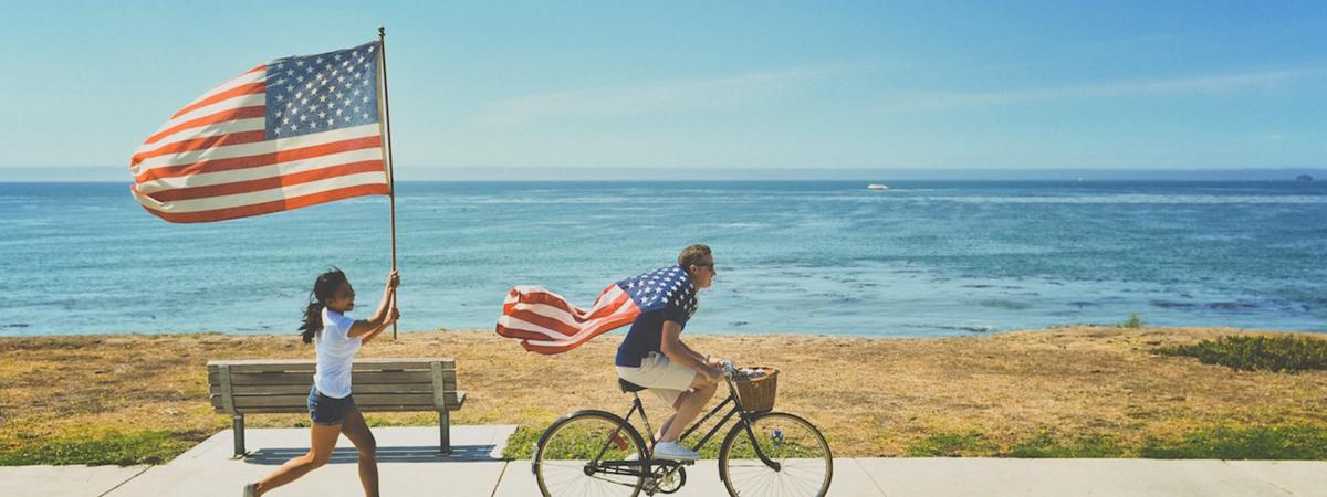 Girl waving a US flag and man on bicycle